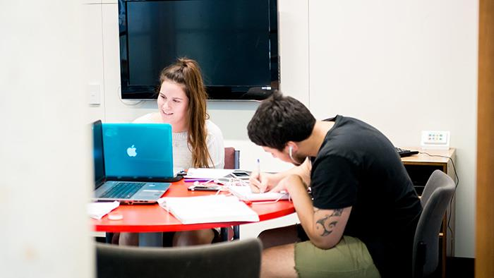 A photograph of two people studying at a table together