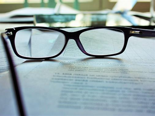 A photograph of a pair of reading glasses on some papers