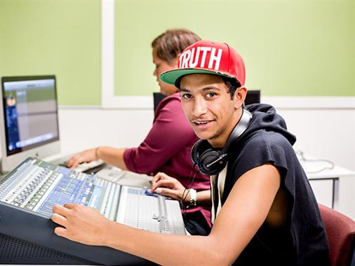 A photograph of a young Maori man at a computer