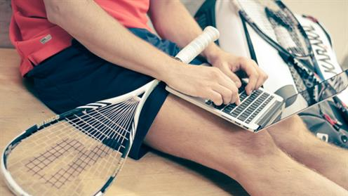 A close-up photograph of a person holding a squash racquet while using a laptop.