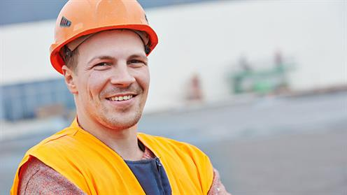 A photograph of a man wearing a hard hat on a work site