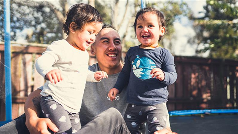A photograph of a Maori man with two toddlers in a playground