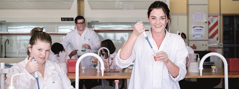 A photograph of students in a science laboratory at UCOL injecting liquid into beakers