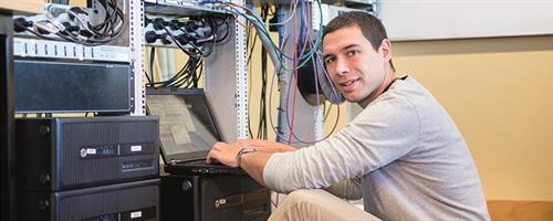A photograph of a man using a laptop next to networking equipment