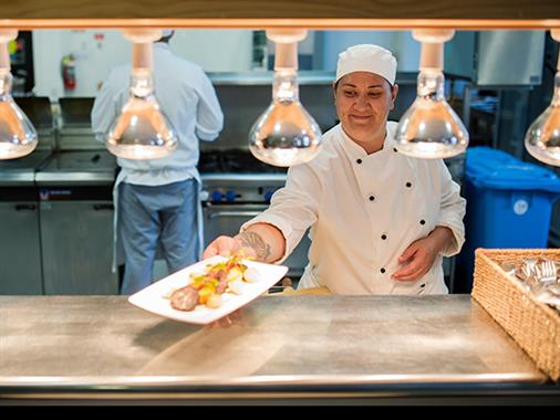A chef delivering a meal for service in a commercial kitchen